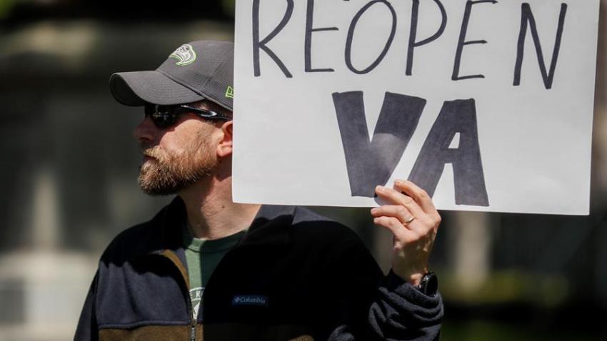 Un hombre sostiene una pancarta durante una protesta contra el confinamiento en Richmond, Virginia.