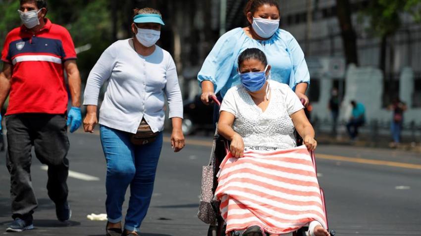 Tres mujeres transitan en San Salvador con mascarillas.
