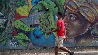 Un joven con tapabocas camina frente a un mural en Tegucigalpa (Honduras)