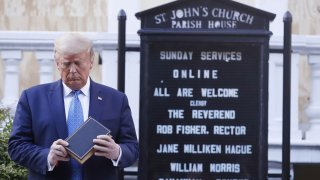 President Donald Trump looks at his Bible in front of St. John's Church.