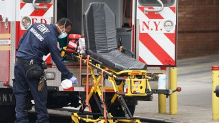 An FDNY paramedic disinfects the ambulance equipment after bringing a patient to Wyckoff Hospital in the Bushwick section of Brooklyn April 5, 2020 in New York