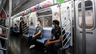 Commuters wearing protective masks ride a subway in New York