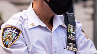 A New York Police Department (NYPD) officer wearing a mask has his badge number covered up with a black strip of fabric in Columbus Circle.