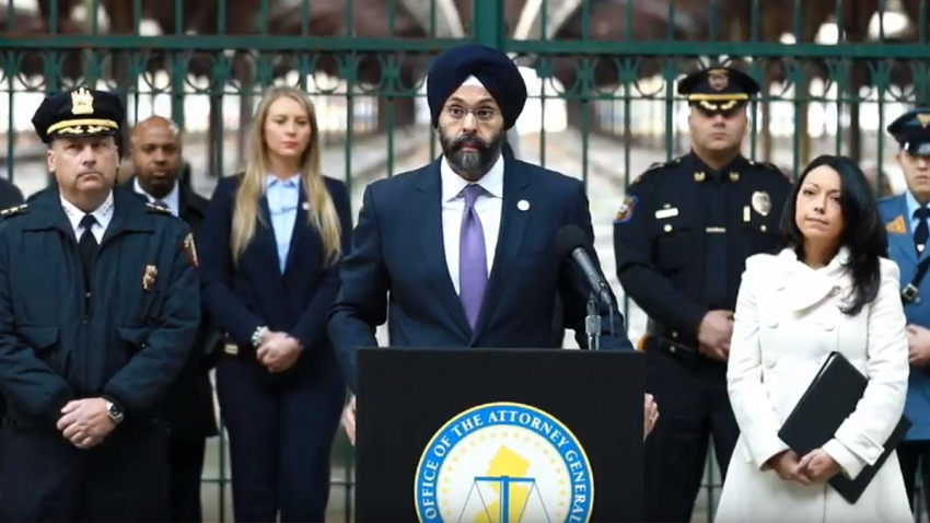 New Jersey Attorney General Gurbur Grewal stands at a podium and is flanked by police officers.
