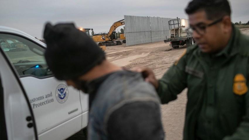 Un agente de la Patrulla Fronteriza de los Estados Unidos detiene a un inmigrante indocumentado cerca de una sección del muro fronterizo de construcción privada el 11 de diciembre de 2019 cerca de Mission, Texas.