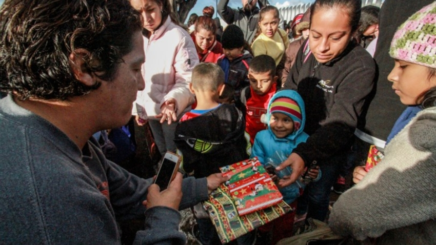Migrantes reciben regalos navideños.