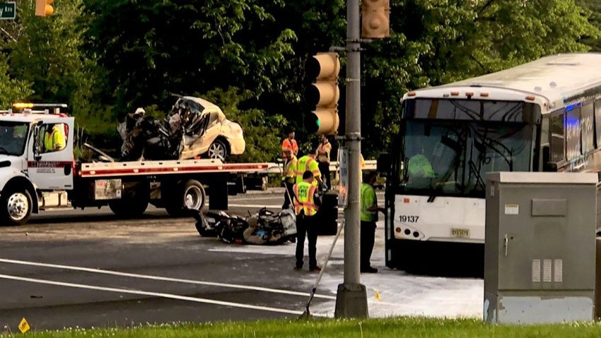 A totaled sedan sits on the bed of a tow truck as the NJ Transit bus with wich it collided rests near the sidewalk in Moorestown, New Jersey.