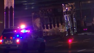 Police surround a tractor trailer that caught fire along the New Jersey Turnpike, killing 10 horses inside.