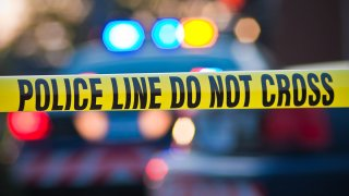 Police lights flashing behind police caution tape