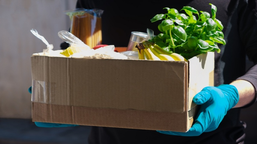 Home delivery during an epidemic. contactless delivery. Food donation. Men's hands hold a box with products.