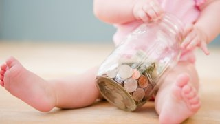 Baby holding jar of money