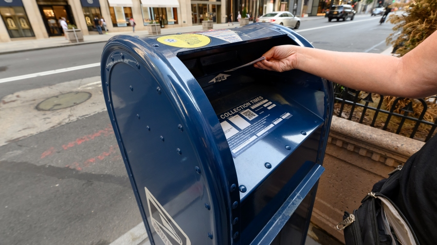 A person drops a letter into a USPS mailbox