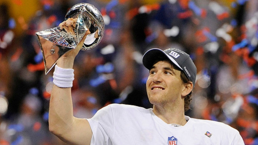 Quarterback Eli Manning #10 of the New York Giants celebrates holding up the Vince Lombardi Trophy after they defeated the New England Patriots in Super Bowl XLVI February 5, 2012