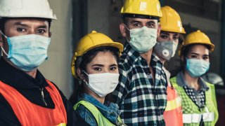 Factory workers with face masks to protect against an outbreak of coronavirus or COVID-19.