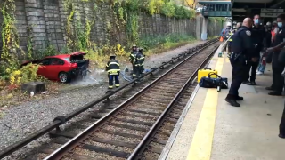 Officials work to remove a sedan that fell near the tracks