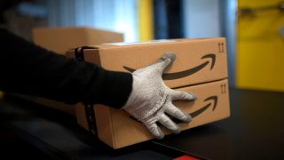 An employee carries a package at the distribution center of US online retail giant Amazon