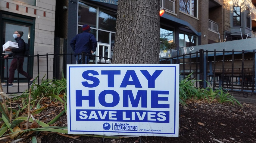 A sign along the sidewalk in an area lined with bars and restaurants in the Wicker Park neighborhood encourages people to stay home