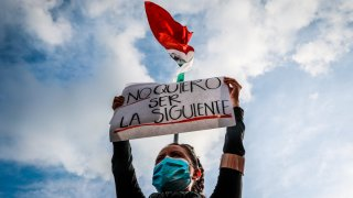Mujer con cubrebocas alza una pancarta de protesta por los feminicidios