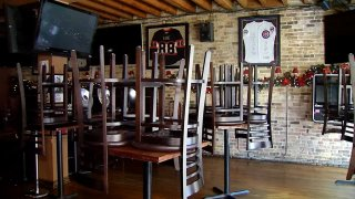 The interior of an empty dining room in a Chicago restaurant, with chairs on tables, sports jerseys on the walls and no customers in the establishment