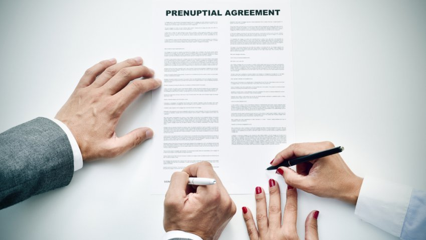 Foto de una pareja simulando firmar un acuerdo prematrimonial.