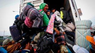 Migrantes bajan de un camión en el que cruzaban México