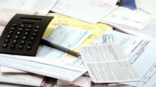 Foto de calculadora, bolígrafo y facturas de utilidades.