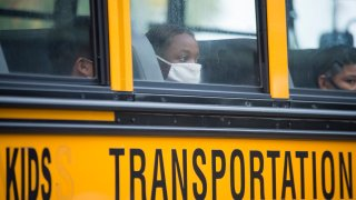 A student wearing a face mask peers out of a school bus window.