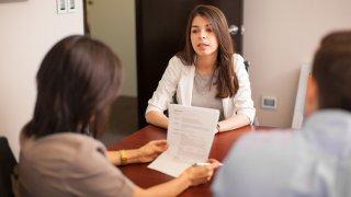 Mujer sentada frente a dos personas que la entrevistan para un empleo.