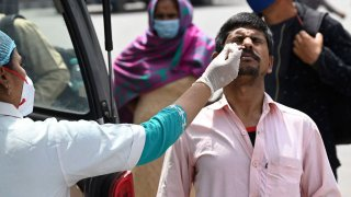 In this March 24, 2021, file photo, a health worker collects a swab sample from a man for the COVID-19 Rapid Antigen Test (RAT) at the Inter-State Bus Terminus (ISBT), in New Delhi.