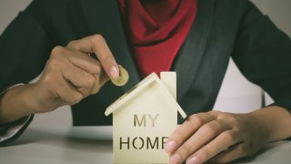 mujer toma una moneda en una mano y en la otra sostiene una alcancía con forma de casa