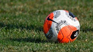 A soccer ball sits on a grass field