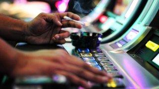 Closeup of a person smoking a cigarette at a casino machine