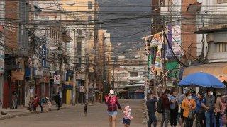 Algunos ciudadanos caminan por una calle comercial durante la jornada de confinamiento en Cochabamba (Bolivia).