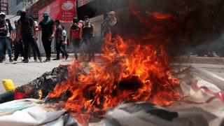Fogata en la que se quema propaganda electoral; a lo lejos se ve a un grupo de jóvenes que protestan