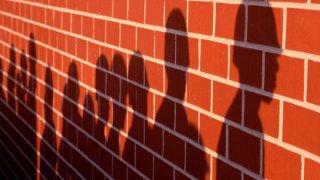 Shadows of marine recruits against a brick wall.