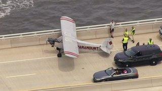 A plane lands on a bridge