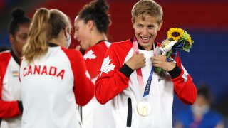 Quinn wears their gold medal after Team Canada's soccer victory