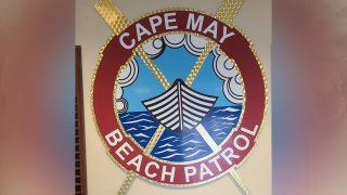 """The Cape May Beach Patrol logo depicts a circle with a boat sailing through the ocean. A red band with the words """"Cape May Beach Patrol"""" is seen around the circle."""
