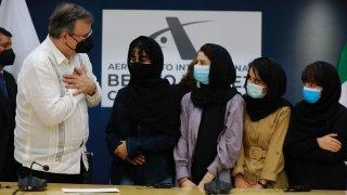 Un funcionario mexicano saluda a cuatro mujeres afganas, de las cinco, que obtuvieron refugio en México