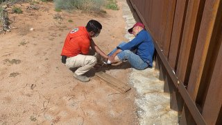 Paramédico auxilia a migrante que cayó del muro fronterizo