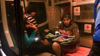 Fotografía de una socorrista de Cruz Roja que carga a un bebé de brazos, mientras un niño la observa