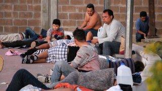 Fotografía de varios hombre y un niño que forman parte de un grupo de migrantes en una bodega