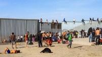 A pesar de la presencia de los agentes, una veintena de integrantes de la caravana migrante escaló los postes de metal que hacen la función de muro divisorio.