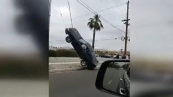 Carro termina colgado de los cables de un poste de luz