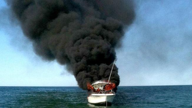 Rescatan a ocupante de barco incendiado